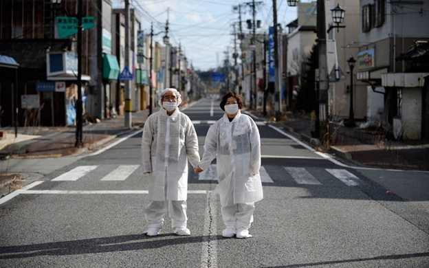 Wearing white protective masks and suits, Yuzo Mihara  and his wife Yuko pose for photographs on a deserted street in the town of Namie, inside the Fukushima nuclear disaster exclusion zone