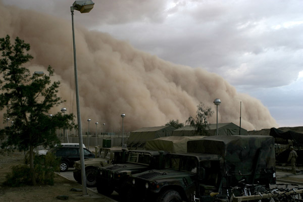 A massive sand storm cloud is close to enveloping a military camp as it rolls over Al Asad, Iraq