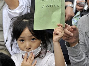 Descrição: Japan, Tokyo: A girl holds her petition to ask the education ministry to protect children from radioactive contamination at Fukushima prefecture. (AFP Photo / Yoshikazu Tsuno)