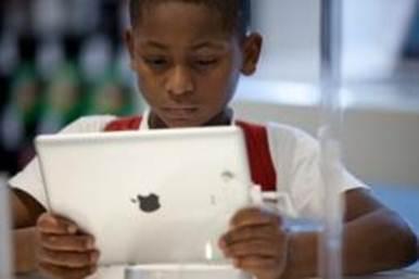 Descrição: A Brazilian boy looks at an iPad