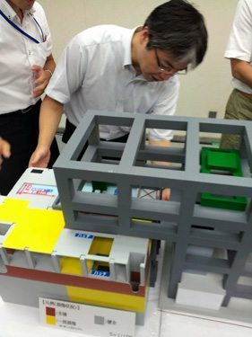 Descrição: Tokyo Electric Power Co. officials use a scale model on Aug. 30 to demonstrate how they plan to cover the No. 4 reactor building of the Fukushima No. 1 nuclear power plant. (Takashi Sugimoto)
