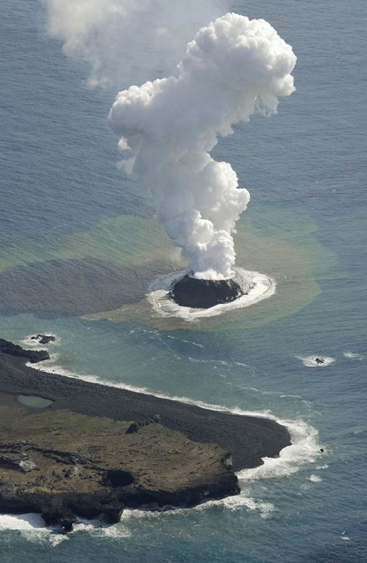 Smoke billows from a new island off the coast of Nishinoshima, seen at bottom, a small, uninhabited island in the Ogasawara chain, far south of Tokyo Thursday, Nov. 21, 2013. The Japan Coast Guard and earthquake experts said a volcanic eruption has raised the new island in the seas to the far south of Tokyo. The coast guard issued an advisory Wednesday warning of heavy black smoke from the eruption. (AP Photo/Kyodo News) JAPAN OUT, MANDATORY CREDIT