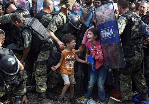 Children cry as migrants waiting on the Greek side of the border break through a cordon of Macedonian special police forces to cross into Macedonia, near the southern city of Gevgelija, The Former Yugoslav Republic of Macedonia on Aug. 21, 2015.