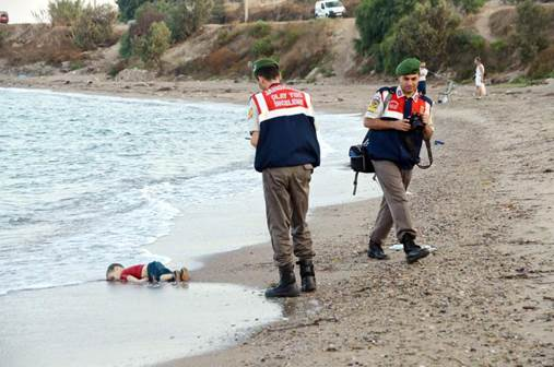 Turkish gendarmerie stand near by the washed up body of a refugee child who drowned during a failed attempt to sail to the Greek island of Kos, at the shore in the coastal town of Bodrum, Turkey on 02 Sept.r 2015.