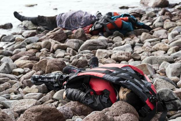 The lifeless bodies of migrants lay on the shoreline near to the Aegean town of Ayvacik, Canakkale, Turkey, Saturday, Jan. 30, 2016.  A boat carrying ...