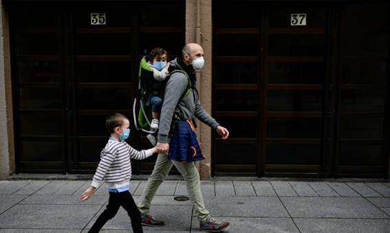 A father with his children wearing face mask to prevent the coronavirus go for a walk at Carlos III promenade, in Pamplona, northern Spain, Sunday, April 27, 2020. (Alvaro Barrientos/AP Photo)