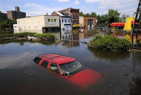 Flood waters from the Passiac River fill the streets covering automobiles including a Chevrolet SUV days after Hurricane Irene in Paterson, New Jersey